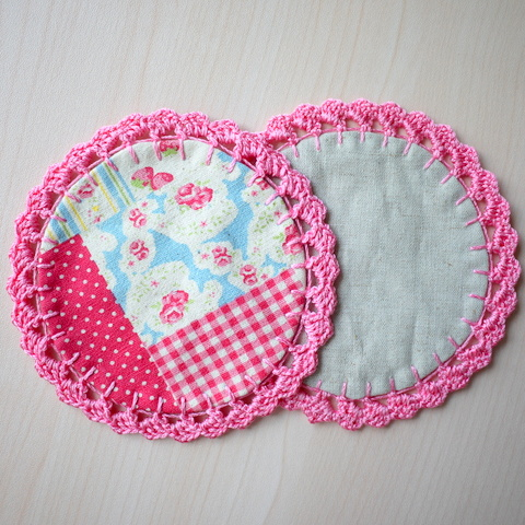 two circular coasters with crochet trim
