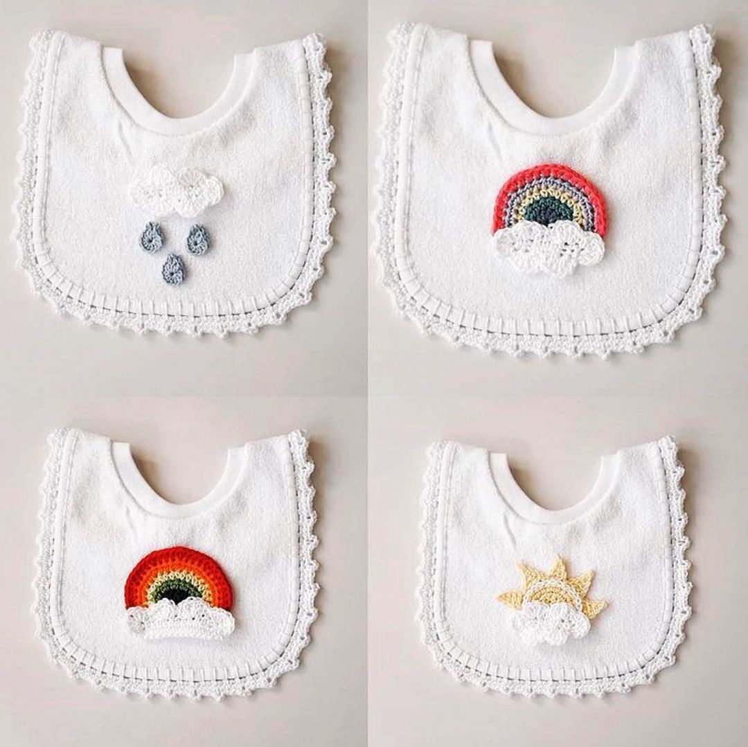 four white bibs with appliques