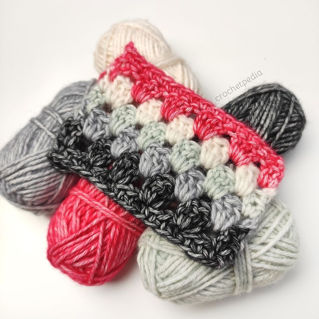 swatch of granny stitch in bright red, greys and black