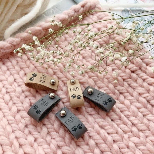 leather labels on pastel pink knitwear
