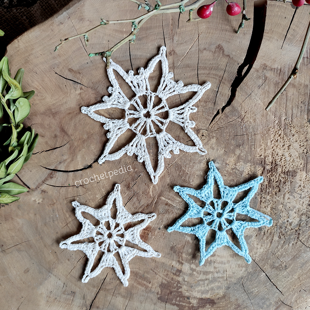 two sizes of snowflakes on wood