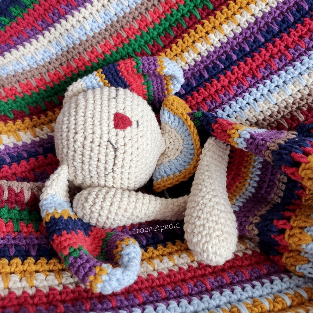 colorful bunny sleeping on a striped blanket