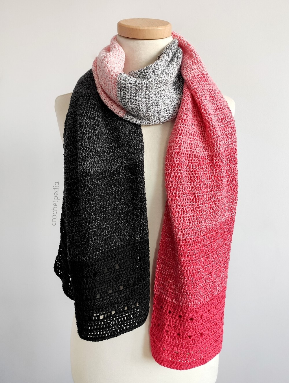 red and black crochet scarf draped on a mannequin