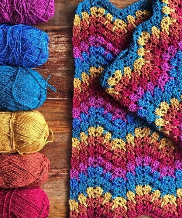 zig-zag blanket on wood with yarn skeins