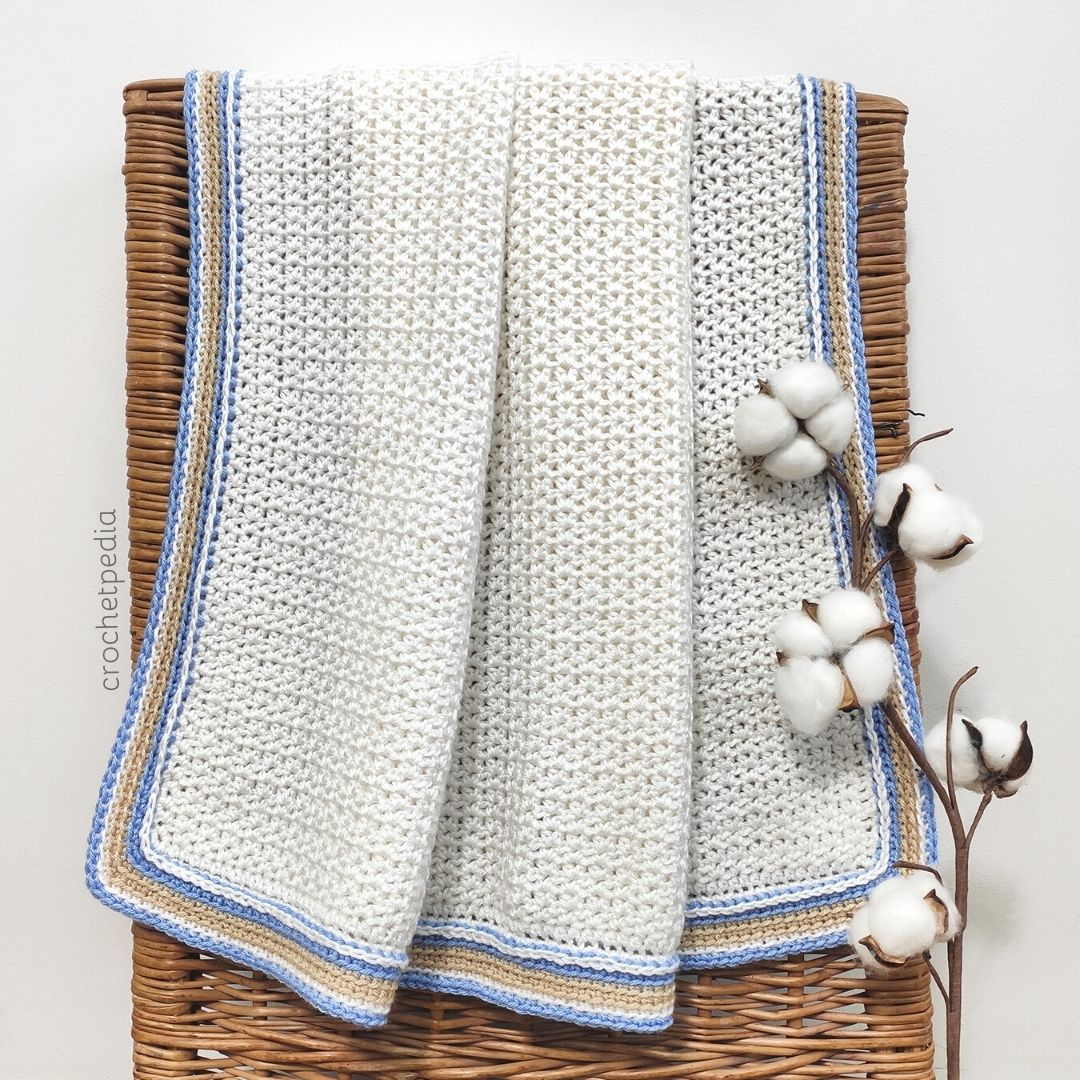 white crochet blanket with cotton flower